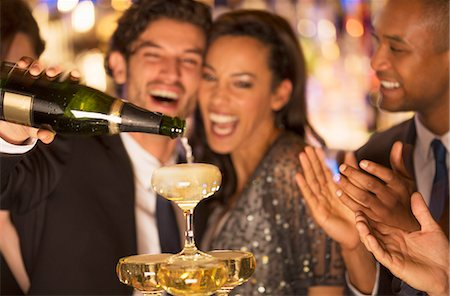 Close up of laughing couple pouring champagne pyramid Stock Photo - Premium Royalty-Free, Code: 6113-07159906
