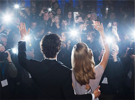 Celebrity couple waving to paparazzi at red carpet event Stock Photo - Premium Royalty-Free, Code: 6113-07159913