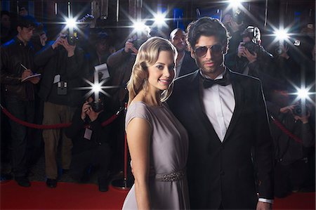 Serious celebrity couple on red carpet with paparazzi in background Stock Photo - Premium Royalty-Free, Code: 6113-07159911