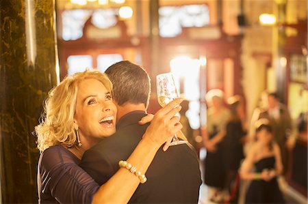 Enthusiastic woman with champagne hugging man in theater lobby Stock Photo - Premium Royalty-Free, Code: 6113-07159926