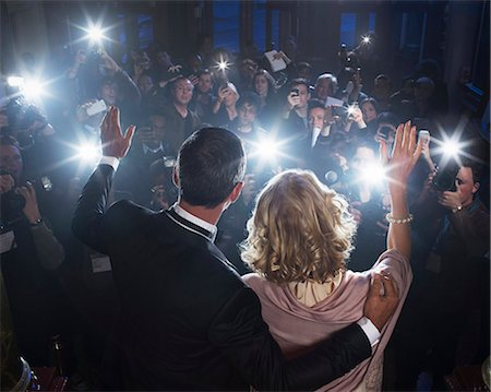 Celebrity couple waving to paparazzi at red carpet event Stock Photo - Premium Royalty-Free, Code: 6113-07159929
