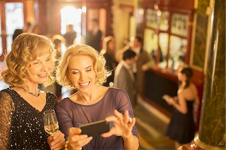 Well dressed women looking at cell phone in theater lobby Stock Photo - Premium Royalty-Free, Code: 6113-07159930