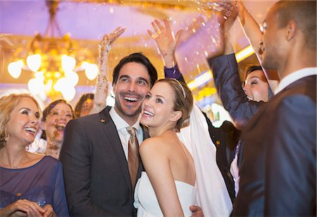 Friends throwing confetti over bride and groom at wedding reception Stock Photo - Premium Royalty-Free, Code: 6113-07160040