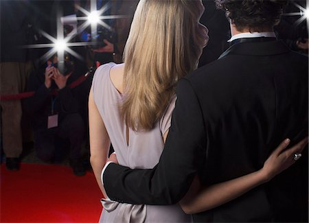 Close up rear view of celebrity couple hugging for paparazzi on red carpet Stock Photo - Premium Royalty-Free, Code: 6113-07160048