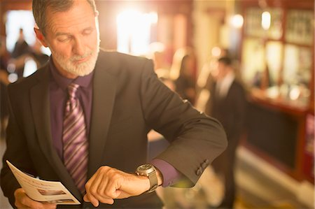 Close up of well dressed man with playbill checking the time in theater lobby Stock Photo - Premium Royalty-Free, Code: 6113-07160049