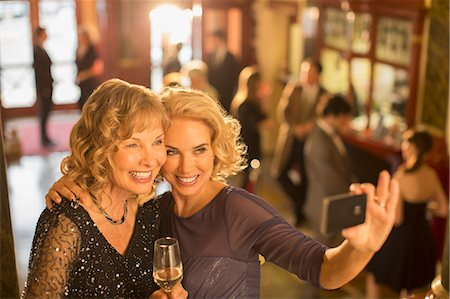 Well dressed women with champagne taking self-portrait with camera phone in theater lobby Stock Photo - Premium Royalty-Free, Code: 6113-07160057