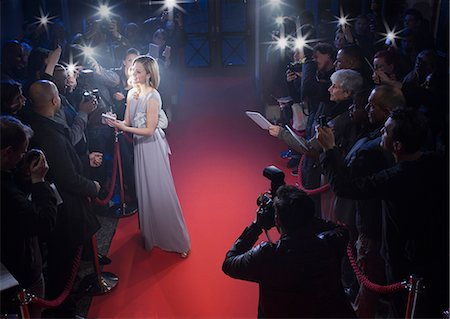 Well dressed female celebrity signing autographs and posing for paparazzi on red carpet Stock Photo - Premium Royalty-Free, Code: 6113-07160054