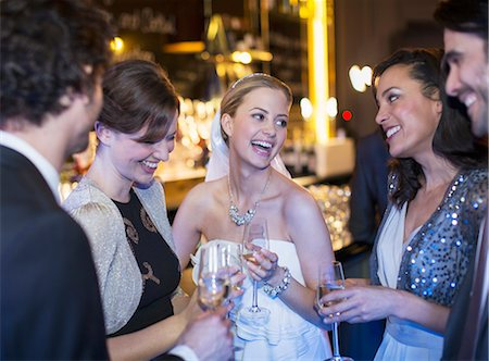 Happy bride drinking champagne with friends at wedding reception Stock Photo - Premium Royalty-Free, Code: 6113-07160055
