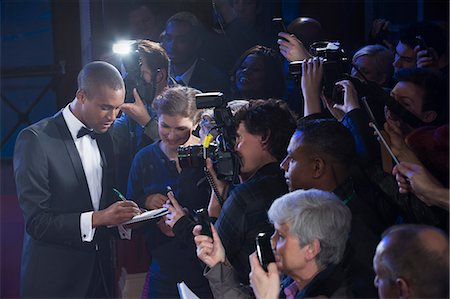 Well dressed male celebrity signing autographs at red carpet event Stock Photo - Premium Royalty-Free, Code: 6113-07160058