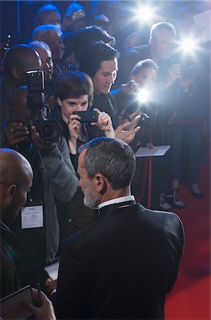 Well dressed male celebrity signing autographs at red carpet event Stock Photo - Premium Royalty-Free, Code: 6113-07160059