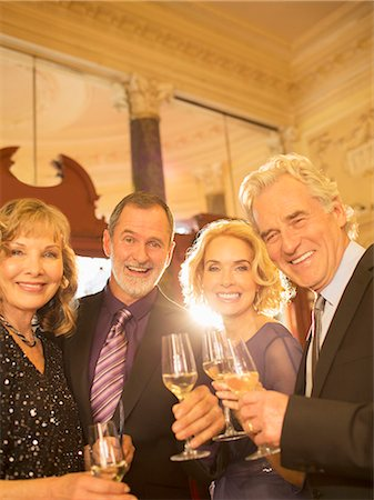 Portrait of well dressed friends drinking champagne in theater lobby Stock Photo - Premium Royalty-Free, Code: 6113-07160062