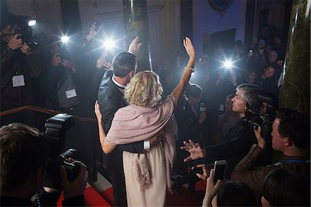 Rear view of well dressed celebrity couple waving to paparazzi on red carpet Stock Photo - Premium Royalty-Free, Code: 6113-07160064