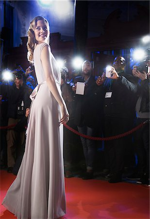 Well dressed female celebrity posing for paparazzi on red carpet Stock Photo - Premium Royalty-Free, Code: 6113-07160073