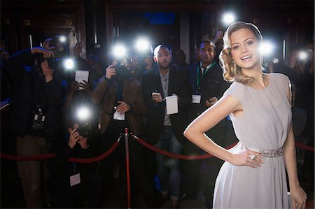 Portrait of well dressed female celebrity at red carpet event with paparazzi in background Stock Photo - Premium Royalty-Free, Code: 6113-07160072