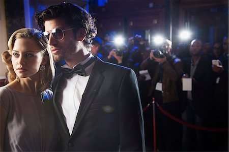 Close up of well dressed celebrity at red carpet event with paparazzi in background Stock Photo - Premium Royalty-Free, Code: 6113-07160074