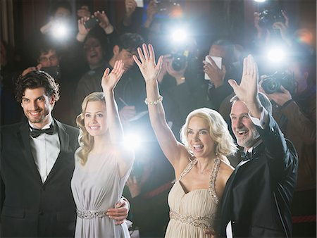 Well dressed celebrity couples waving to paparazzi at red carpet event Stock Photo - Premium Royalty-Free, Code: 6113-07160078