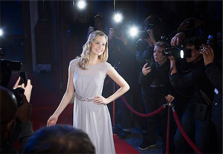 Well dressed female celebrity posing for paparazzi on red carpet Stock Photo - Premium Royalty-Free, Code: 6113-07160081