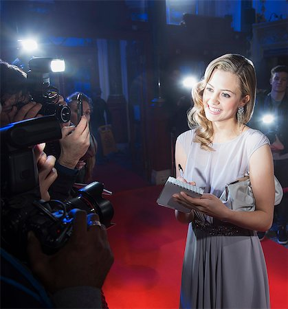 Well dressed female celebrity signing autograph and posing for paparazzi on red carpet Stock Photo - Premium Royalty-Free, Code: 6113-07160082