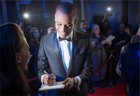 Well dressed celebrity signing autograph on red carpet Stock Photo - Premium Royalty-Free, Code: 6113-07160085