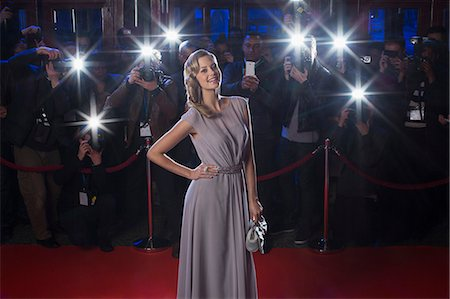 Portrait of well dressed female celebrity on red carpet with paparazzi in background Stock Photo - Premium Royalty-Free, Code: 6113-07160010
