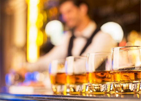 Close up of bourbon in glasses in a row on bar Stock Photo - Premium Royalty-Free, Code: 6113-07160011