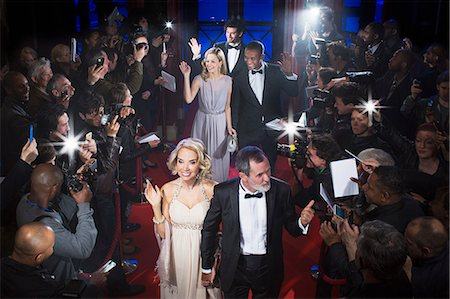 Well dressed celebrities waving to paparazzi on red carpet Stock Photo - Premium Royalty-Free, Code: 6113-07160023