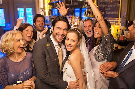 Friends cheering around smiling bride and groom at wedding reception Stock Photo - Premium Royalty-Free, Code: 6113-07160029