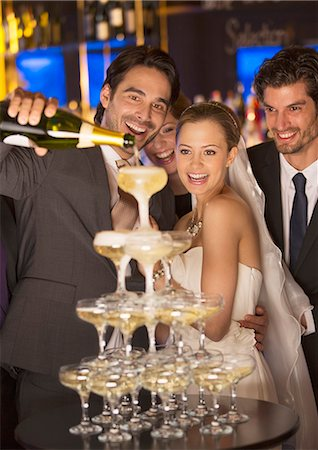 Groom pouring champagne pyramid at wedding reception Stock Photo - Premium Royalty-Free, Code: 6113-07160033
