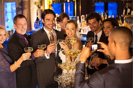 Man photographing bride and groom with friends at champagne pyramid Stock Photo - Premium Royalty-Free, Code: 6113-07160036