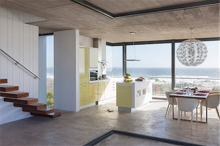 Modern kitchen and dining room overlooking ocean Stock Photo - Premium Royalty-Free, Code: 6113-07160167