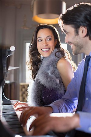 Close up of well dressed couple playing piano in lounge Stock Photo - Premium Royalty-Free, Code: 6113-07160130