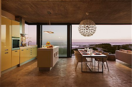 Modern kitchen and dining room overlooking ocean at sunset Stock Photo - Premium Royalty-Free, Code: 6113-07160138