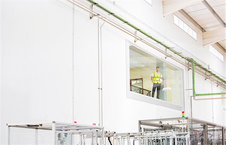supervising - Worker looking out glass window in warehouse Stock Photo - Premium Royalty-Free, Code: 6113-07160256