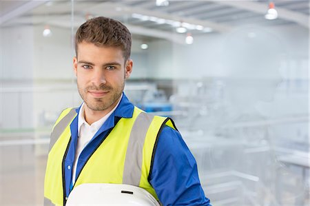 security - Worker smiling by window in factory Stock Photo - Premium Royalty-Free, Code: 6113-07160279