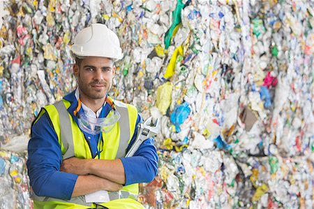 Worker standing by compacted recycling bundles Stock Photo - Premium Royalty-Free, Code: 6113-07160283