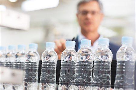 Supervisor examining bottles in factory Stock Photo - Premium Royalty-Free, Code: 6113-07160295