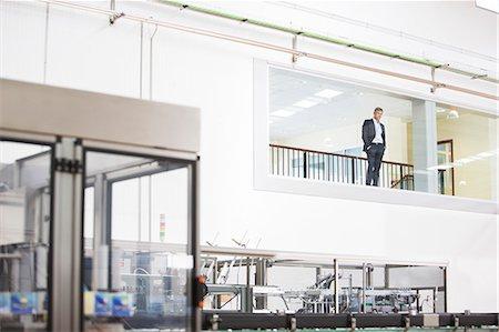 people working in factory - Businessman in window overlooking factory Stock Photo - Premium Royalty-Free, Code: 6113-07160321