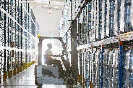 Worker operating forklift in warehouse Stock Photo - Premium Royalty-Free, Code: 6113-07160322