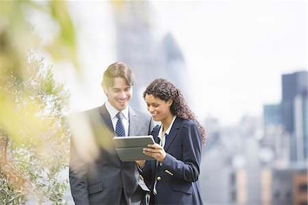 Business people using digital tablet outdoors Stock Photo - Premium Royalty-Free, Code: 6113-07160451