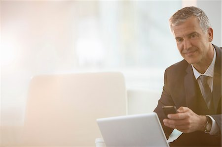 Businessman using cell phone and laptop in office Stock Photo - Premium Royalty-Free, Code: 6113-07160473