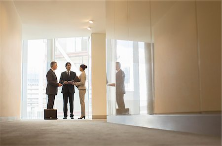 Business people talking at office window Stock Photo - Premium Royalty-Free, Code: 6113-07160482
