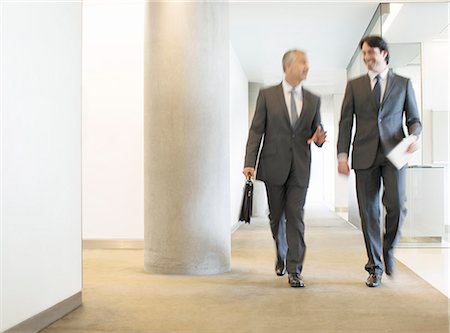 Businessmen talking in office corridor Stock Photo - Premium Royalty-Free, Code: 6113-07160494