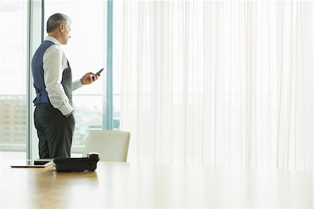 Businessman using cell phone in office Stock Photo - Premium Royalty-Free, Code: 6113-07160421