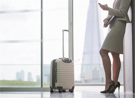 Businesswoman with suitcase in airport Stock Photo - Premium Royalty-Free, Code: 6113-07160426