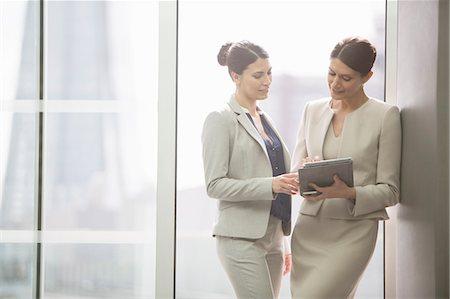 Businesswomen using digital tablet in office Stock Photo - Premium Royalty-Free, Code: 6113-07160431