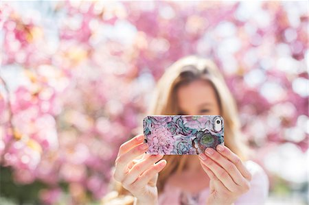 Woman taking self-portrait with cell phone outdoors Stock Photo - Premium Royalty-Free, Code: 6113-07160583