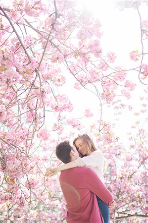 spring - Couple hugging under tree with pink blossoms Stock Photo - Premium Royalty-Free, Code: 6113-07160586