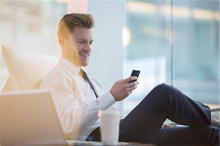 Businessman using cell phone in office Stock Photo - Premium Royalty-Free, Code: 6113-07160510