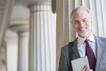 pillar - Businessman smiling outdoors Stock Photo - Premium Royalty-Free, Code: 6113-07160692