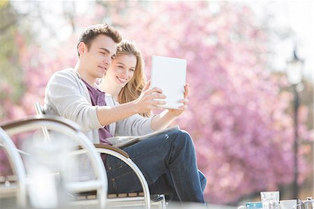 people sitting on bench - Couple using digital tablet in park Stock Photo - Premium Royalty-Free, Code: 6113-07160605